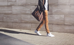 Fashion african man in black rock leather jacket with bag walking over grey textured at evening city Stock Photos