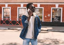 Fashion african man calling on smartphone walking over city street stock photos