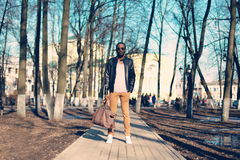 Fashion african man model wearing black leather jacket with bag on street in park royalty free stock images
