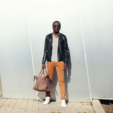 Fashion african man model wearing sunglasses and black leather jacket with bag Stock Photos