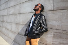Fashion african man relaxing in city over gray background Stock Photos