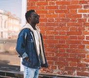 Fashion african man wearing jeans jacket walking on city street stock photo
