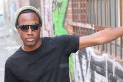 Fashion African man wearing a sunglasses, beanie, piercing and black tee over urban background in city alley royalty free stock image