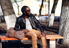 Fashion african man wearing a sunglasses and black leather jacket sits on a bench in the park Royalty Free Stock Photography