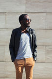 Fashion african man wearing a sunglasses and black rock leather jacket over textured background in city Royalty Free Stock Photography
