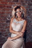 Fashion afro american model in gold dress indoor, Woman elegant golden gown royalty free stock image