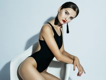 Fashion And People Concept: Beautiful Model Woman In Black Swimsuit Sits In A Chair