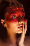 Fashion Art Concept. Beauty Woman Face with Red Painted Mask. Artistic Woman in Red Painted Mask royalty free stock images