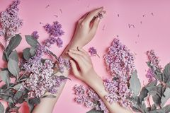 Fashion art hands natural cosmetics women, bright purple lilac flowers in hand with bright contrast makeup, hand care. Creative stock photography