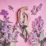 Fashion art hands natural cosmetics women, bright purple lilac flowers in hand with bright contrast makeup, hand care. Creative