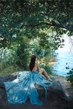 Model Portrait. Girl on a beach. Fashion Art Photo. attractive Woman with naked breast and back in blue dress sitting on rocky beach against watery and trees royalty free stock photo
