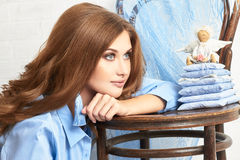 Fashion art photo of a woman in a blue shirt. Naked body. Thoughtful mysterious dreamy portrait of a girl with blue eyes at home Stock Photography