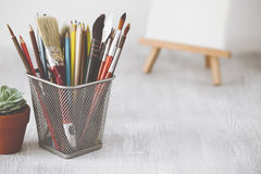 Fashion artist table desk. Creative workspace with paint brushes, pencils, succulent and canvas on easel on background Royalty Free Stock Photography