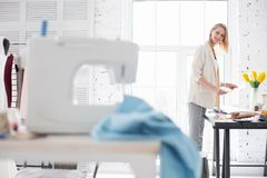 Vigorous ambitious craftswoman planning new collection. Fashion as profession. Joyful glad craftswoman holding sketch while staring at sewing machine Royalty Free Stock Image