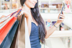 Fashion asian woman with bag using mobile phone, shopping center Royalty Free Stock Photography
