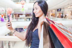 Fashion asian woman with bag using mobile phone, shopping center Stock Photos