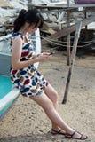 Fashion Asian Woman Playing Mobile Phone at Seaside Stock Image