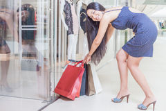 Fashion Asian woman pulls out many bags at mall centre Royalty Free Stock Photos