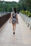 Fashion Asian Woman Walking on Bridge Portrait. Beautiful fashion portrait of asian woman walking on bridge beside beach Royalty Free Stock Images