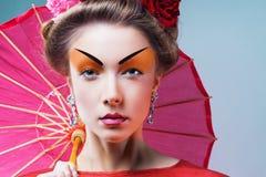 Fashion asian woman wearing traditional japanese red kimono. With umbrella, studio shot.  Geisha Royalty Free Stock Photo