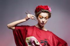 Fashion asian woman wearing traditional japanese red kimono. With umbrella, studio shot.  Geisha Stock Image