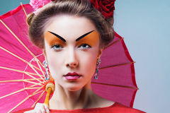 Fashion asian woman wearing traditional japanese red kimono. With umbrella, studio shot.  Geisha Royalty Free Stock Images
