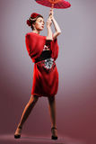 Fashion asian woman wearing traditional japanese red kimono. With umbrella, studio shot.  Geisha Royalty Free Stock Photography