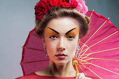 Fashion asian woman wearing traditional japanese red kimono. With umbrella, studio shot.  Geisha Stock Photo