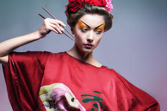 Fashion asian woman wearing traditional japanese red kimono. With umbrella, studio shot.  Geisha Royalty Free Stock Image