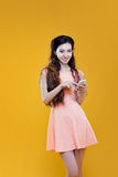 Fashion asian young  girl with mobile phone. Portrait on yellow background Royalty Free Stock Photos