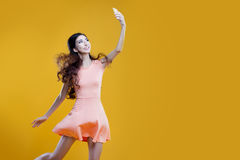Fashion asian young  girl   taking picture of herself, selfie. Yellow background. place for your text on the right Stock Photos