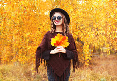 Fashion in autumn colors! portrait smiling woman wearing a black hat knitted poncho with maple leafs over sunny yellow leaves Stock Photos