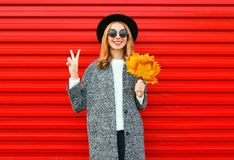 Fashion autumn cool girl with yellow maple leaves. On a red background Royalty Free Stock Photography