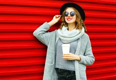 Fashion autumn portrait smiling woman with coffee cup. Is wearing a knitted clothes on a red background royalty free stock image