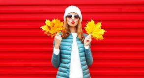Fashion autumn portrait woman holds yellow maple leaves. Blows red lips, sends an air kiss on background in city stock image