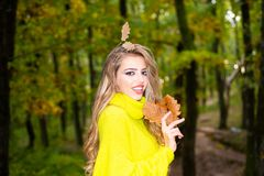 Fashion autumn portrait woman with yellow maple leaves on Nature Background. Pretty woman walking in the Park and stock photos