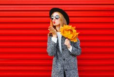 Fashion autumn pretty woman sends an air kiss with yellow maple leaves. Wearing coat on red background Stock Image