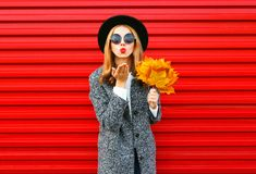 Fashion autumn pretty woman sends an air kiss with yellow maple leaves. Wearing a coat on red background Stock Image