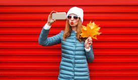 Fashion autumn pretty woman takes a picture self portrait on a smartphone royalty free stock photography