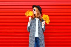 Fashion autumn pretty woman with yellow maple leaves. Wearing a coat on red background royalty free stock photography
