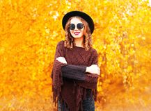 Fashion autumn smiling woman in black round hat, knitted poncho. On a yellow leaves background royalty free stock images