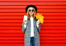 Fashion autumn smiling woman with coffee cup and yellow maple leaves. On red background Stock Photos