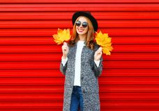 Fashion autumn smiling woman holds yellow maple leaves on a red. Background Stock Photography