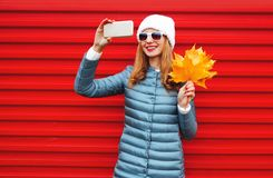 Fashion autumn smiling woman takes a picture self portrait on a smartphone stock image