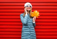 Fashion autumn smiling woman talks on a smartphone. Holds yellow maple leaves in hands on a red background in the city Royalty Free Stock Photo