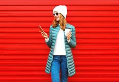 Fashion autumn smiling woman using smartphone holds coffee. Cup on a red background in the city stock photos