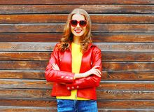 Fashion autumn smiling woman wearing a red leather jacket. On a wooden background Stock Photography
