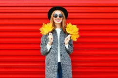 Fashion autumn smiling woman with yellow maple leaves on a red Royalty Free Stock Image