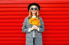 Fashion autumn smiling woman with yellow maple leaves on red Royalty Free Stock Images