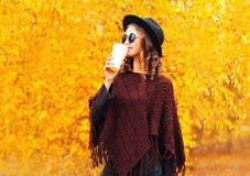 Fashion autumn woman drinks coffee in black round hat, knitted poncho. On a yellow leaves background royalty free stock photo